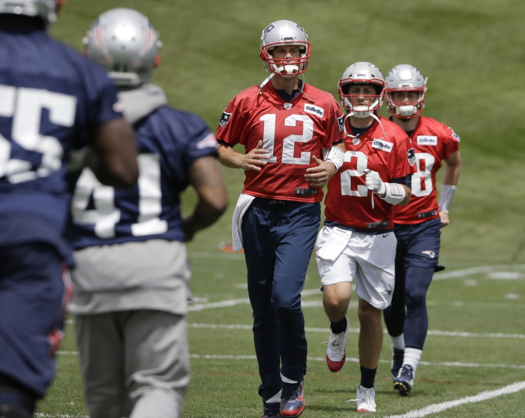New England Patriots quarterbacks Tom Brady (12) Brian Hoyer (2) and Danny Etling, behind right, warm up during an NFL football minicamp practice, Tuesday, June 5, 2018, in Foxborough, Mass. ()