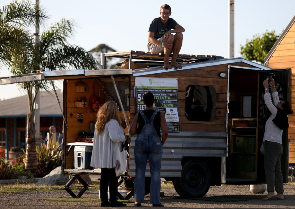 Richard Ward chats with attendees about the boat trailer he converted into a tiny home that he lives in full-time during TinyFest California at the Santa Clara County Fairgrounds in San Jose, Calif., on Friday. The weekend-long event showcases the tiny house movement.