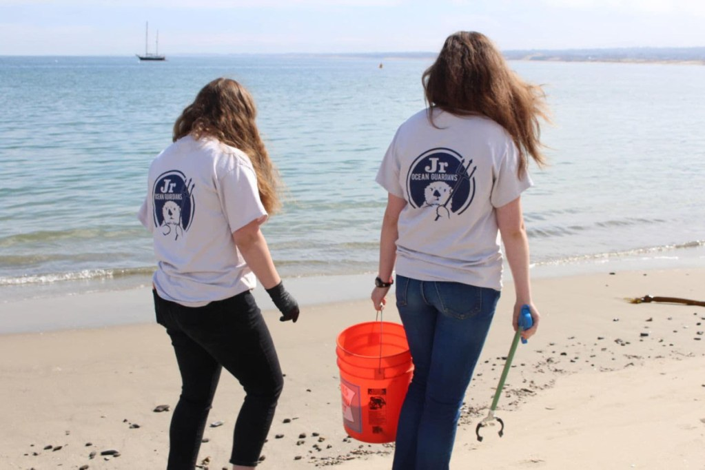 Shelby O'Neil, left, and a friend clean up trash from  a beach in Monterrey, Calif. in 2017.