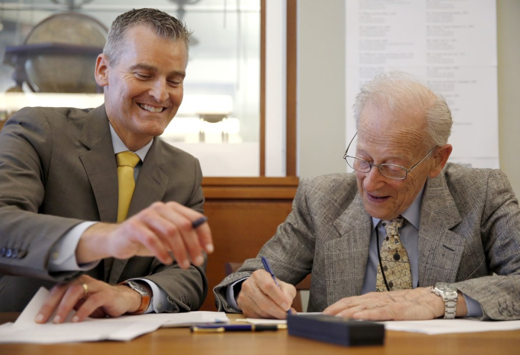 University of Southern Maine President Glenn Cummings, left, and Harold Osher sign documents to make official Osher's donation of maps, valued at $100 million, to the school Friday at the Portland campus.