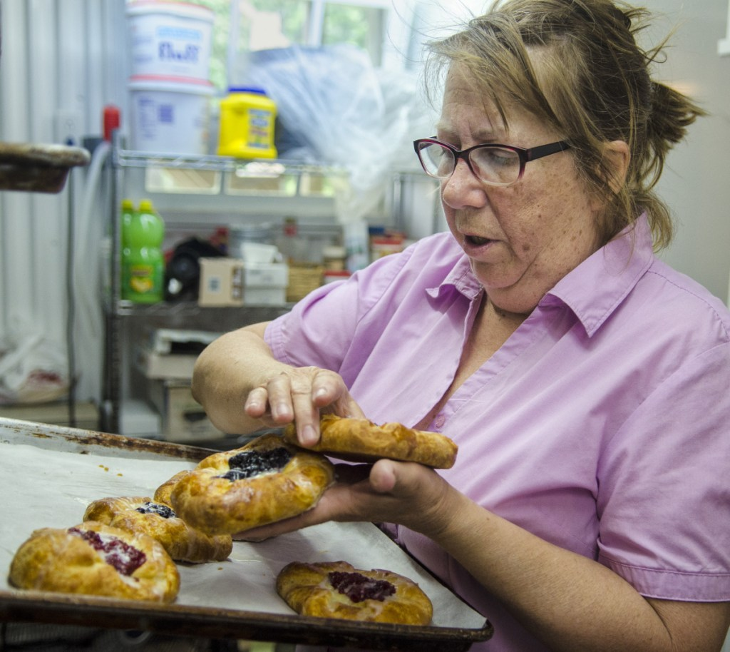 Robin Chase moves Danish pastries from a rack in the back and into the front display case Wednesday at Chase Farm and Bakery in Whitefield.