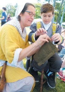 HARRIET BEECHER STOWE ELEMENTARY SCHOOL fifth grader Vito Sullivan gets some tips on sewing from former teacher Lisa Nelson on Friday at Old Brunswick Day. DARCIE MOORE / THE TIMES RECORD