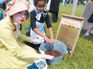 HARRIET BEECHER STOWE ELEMENTARY SCHOOL third graders Elizabeth Wright, left, and Aryanna Burns demonstrate how colonial-era women laundered clothes at Old Brunswick Day. DARCIE MOORE / THE TIMES RECORD