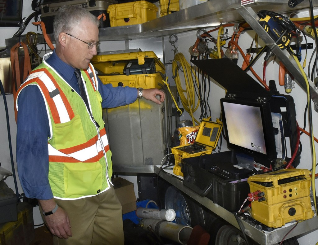 Roger Crouse, general manager of Kennebec Water District, monitors a hard-hat diver making repairs to an underwater 16-inch water line Tuesday in murky Messalonskee Stream off North Riverside Drive in Waterville. The line broke Monday, stirring up sediment in the pipes, causing discoloration in the water, which nevertheless is safe to drink and use, according to the Kennebec Water District.