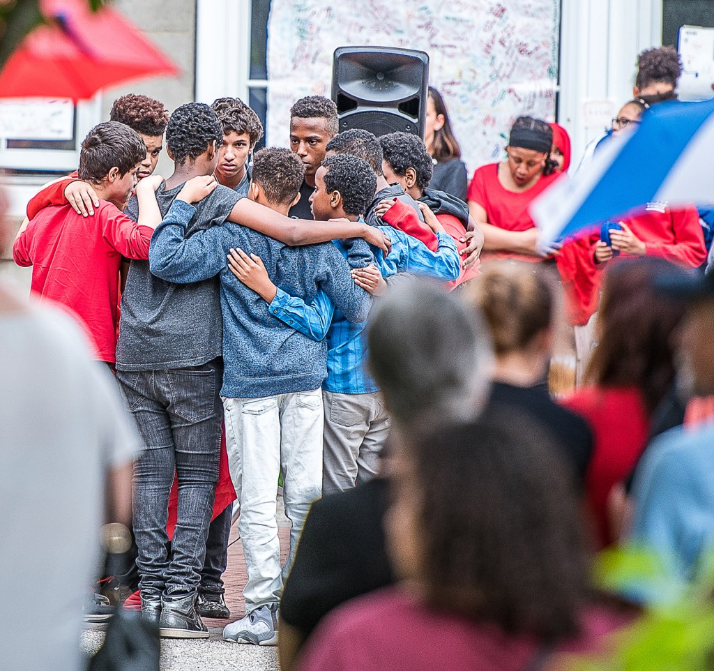 Nine of Rayan Issa's friends form a tight circle at the center of a vigil at Lewiston Middle School on Wednesday night. Rayan apparently drowned during a school trip to Range Pond in Poland on Tuesday.