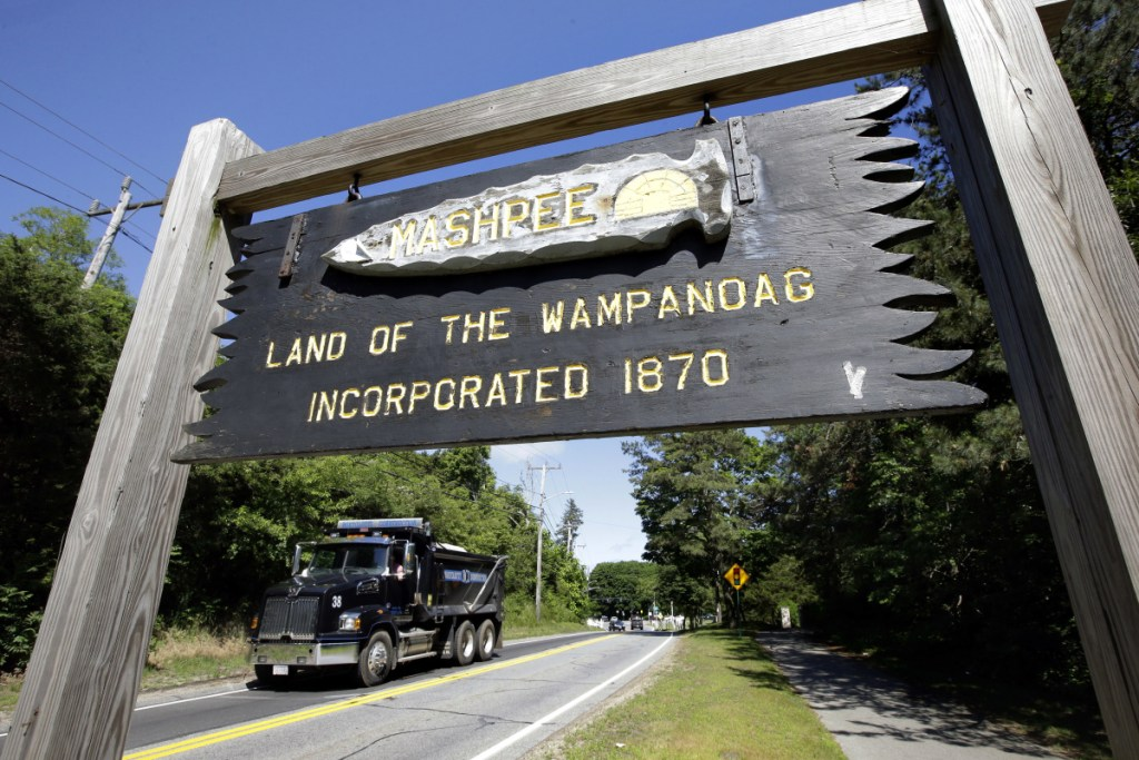 In this Monday, June 25, 2018 photo a wooden sign advises motorists of the location of Mashpee Wampanoag Tribal lands in Massachusetts. The Mashpee Wampanoag Tribe says an unfavorable decision from the U.S. Interior Department on its tribal reservation status would effectively shut down certain government operations, including the tribe's new court system and police force. (AP Photo/Steven Senne)
