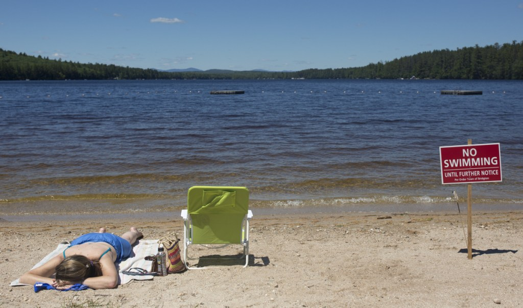 Christy Dow of Naples sunbathes on July 7 at Woods Pond Beach in Bridgton, where a number of people reported falling ill after being in the water.