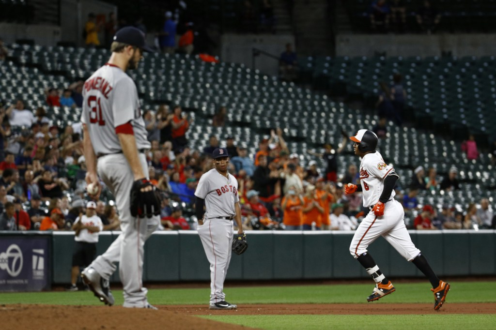 Baltimore's Jonathan Schoop, right, rounds the bases past Boston Red Sox starting pitcher Drew Pomeranz, front left, and third baseman Rafael Devers after hitting a two-run home run in the third inning of the Orioles' 7-6 win over the Red Sox on Tuesday in Baltimore.