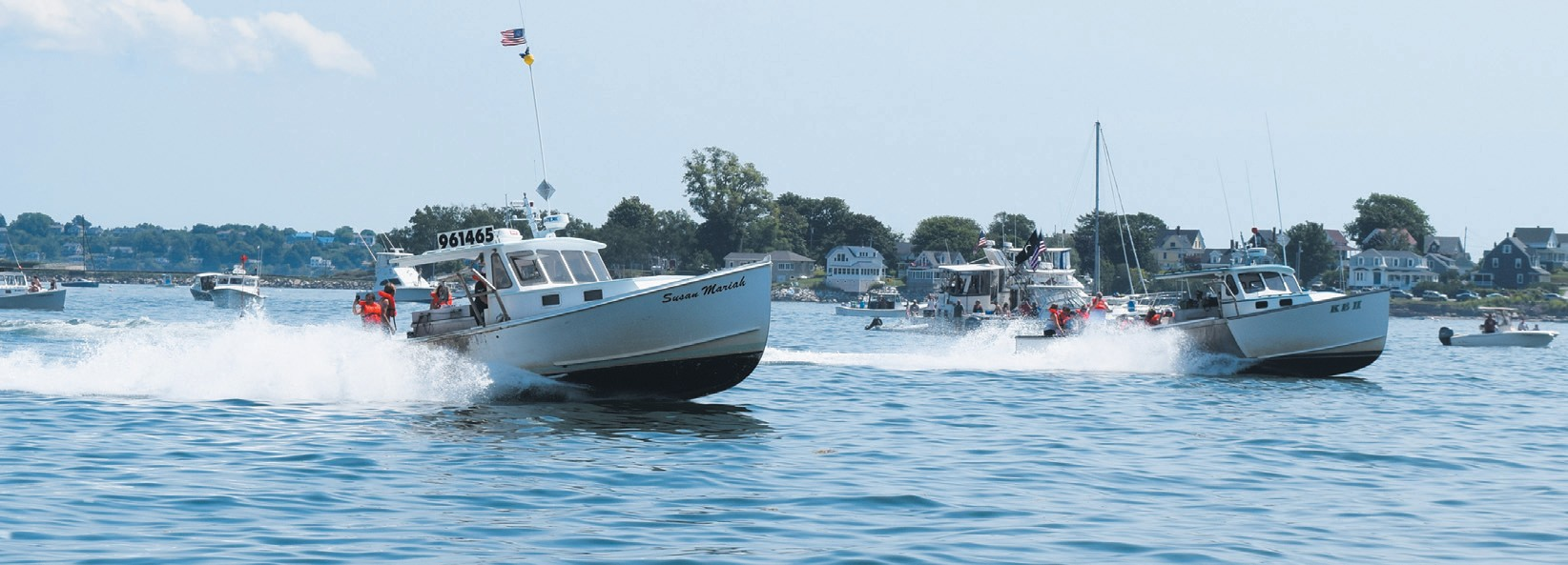 IN THE PHOTO ABOVE, two boats race toward the finish line at the 2018 Harpswell Lobster Boat Races on Sunday. In the photo on the left, people hop between boats, enjoy the sun and have a good time between the races. NATHAN STROUT / THE TIMES RECORD