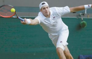 JOHN ISNER of the United States returns the ball to Canada's Milos Raonic during their men's quarterfinal match at the Wimbledon Tennis Championships in London on Wednesday. THE ASSOCIATED PRESS