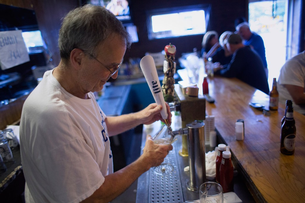 Richard Piacentini, owner of the Forest Gardens bar in Portland, pours a beer on Friday. He's retiring after running the bar for four decades. The new owners plan to keep it essentially the same.