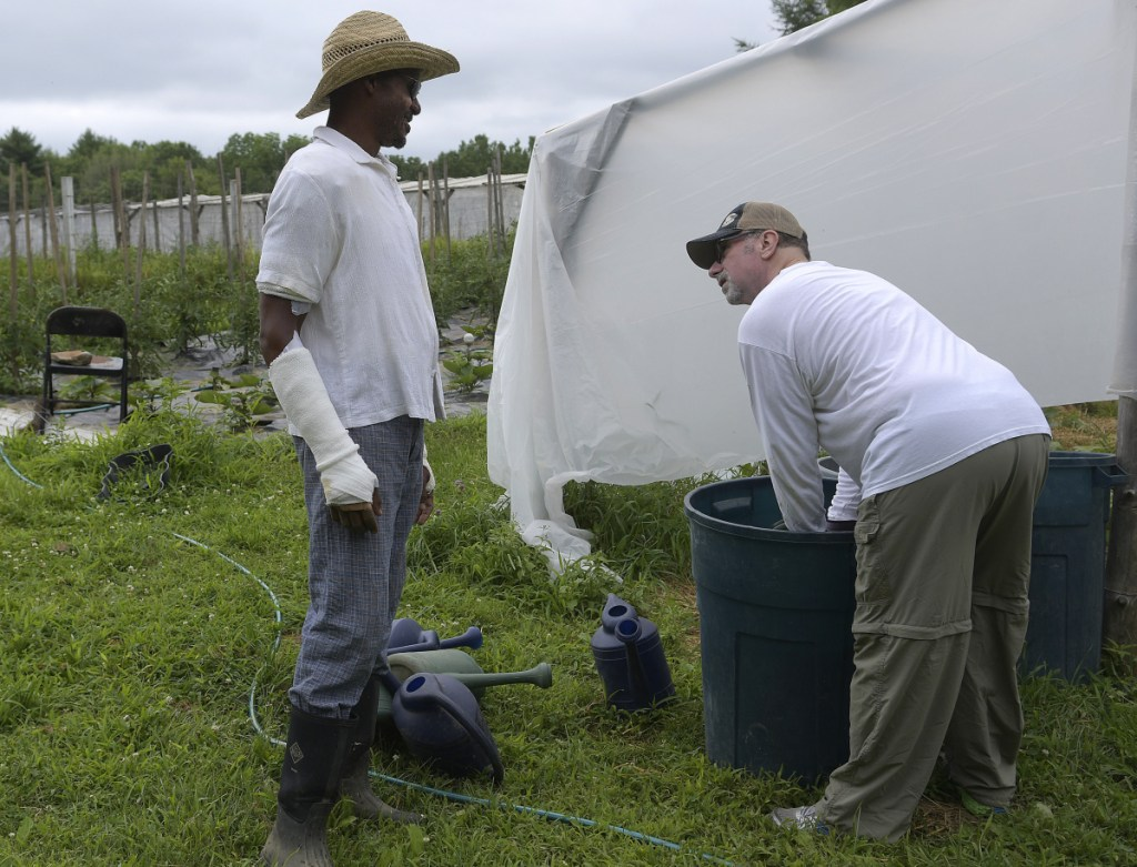 Rep. Craig Hickman, left, speaks Sunday with his neighbor John Branning, who volunteered to fertilize vegetables at the Winthrop farm Hickman operates with his husband, Jop Blom.