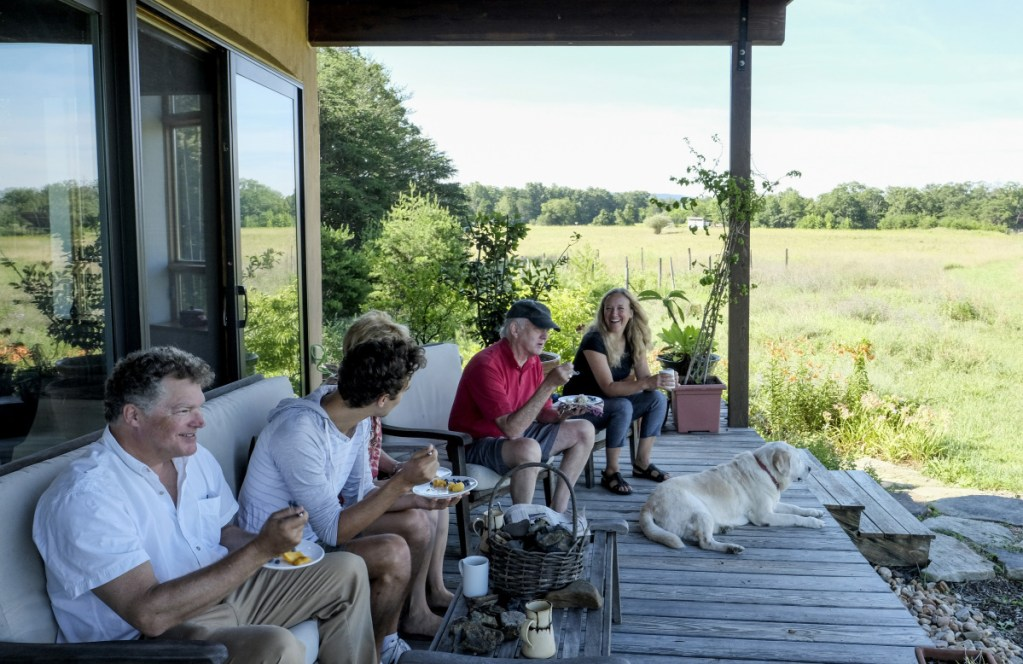 Matthew Grove, left, and his wife Lisa Dall'Olio, right, visit with family and neighbors, on their porch in Gerrardstown, W.Va. Their home is one of 16 planned for the 320-acre Broomgrass farm.