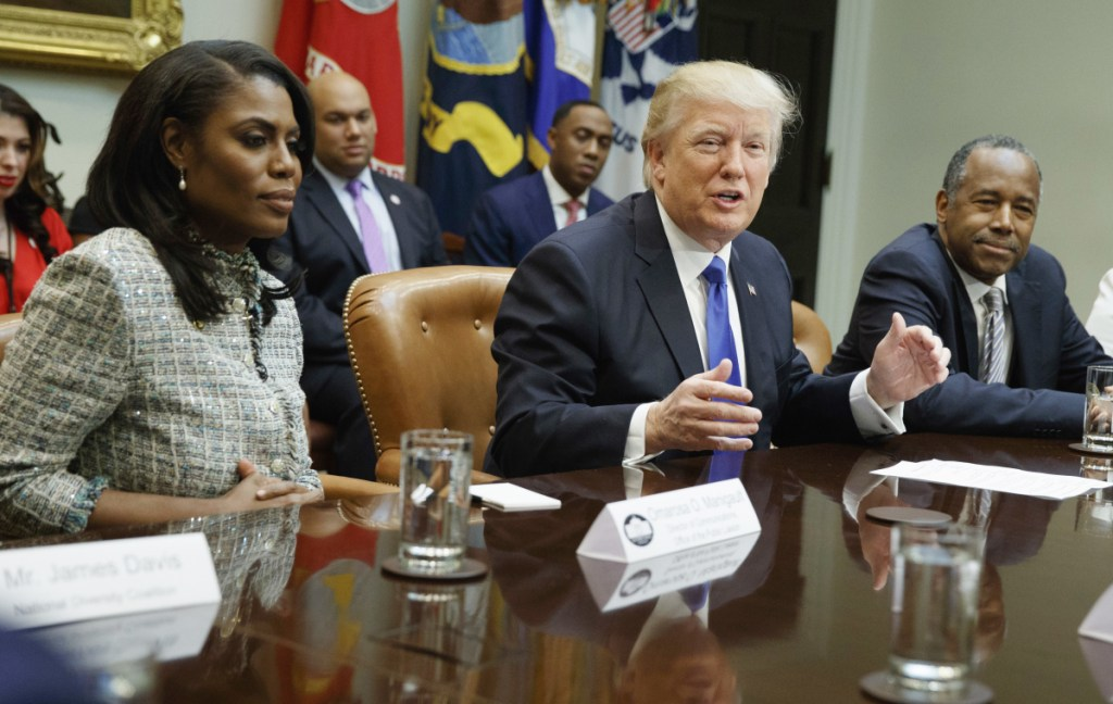 """President Trump is flanked by White House staffer Omarosa Manigault Newman, left, and  then-Housing and Urban Development Secretary-designate Ben Carson as he speaks during a meeting on African American History Month in the Roosevelt Room of the White House in Washington. Manigault Newman, who was fired in December, released a new book """"Unhinged,"""" about her time in the White House."""