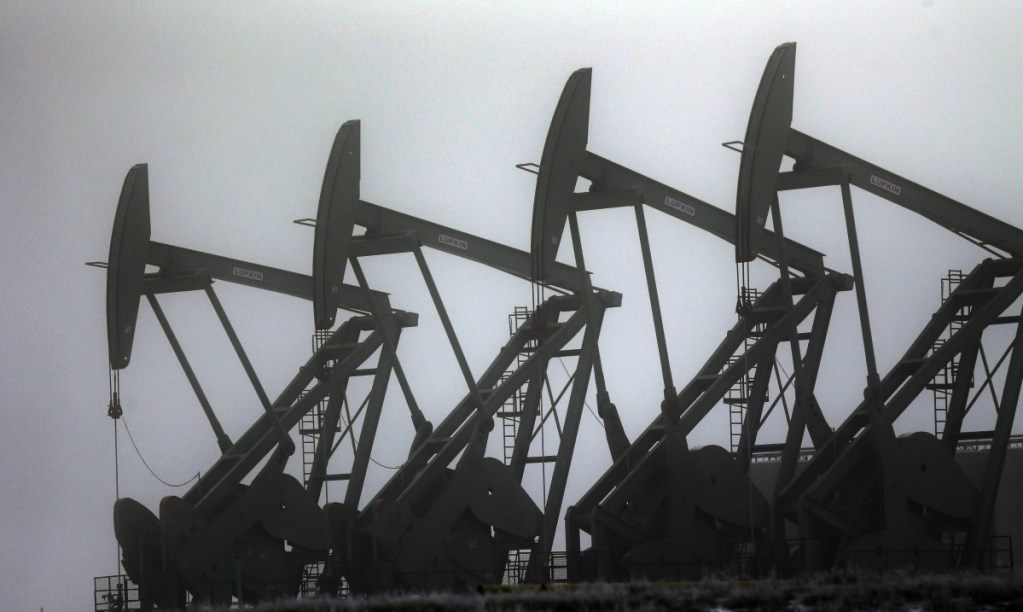 Oil pump jacks work in Williston, N.D. Conserving oil is no longer an economic imperative, the Energy Department says.