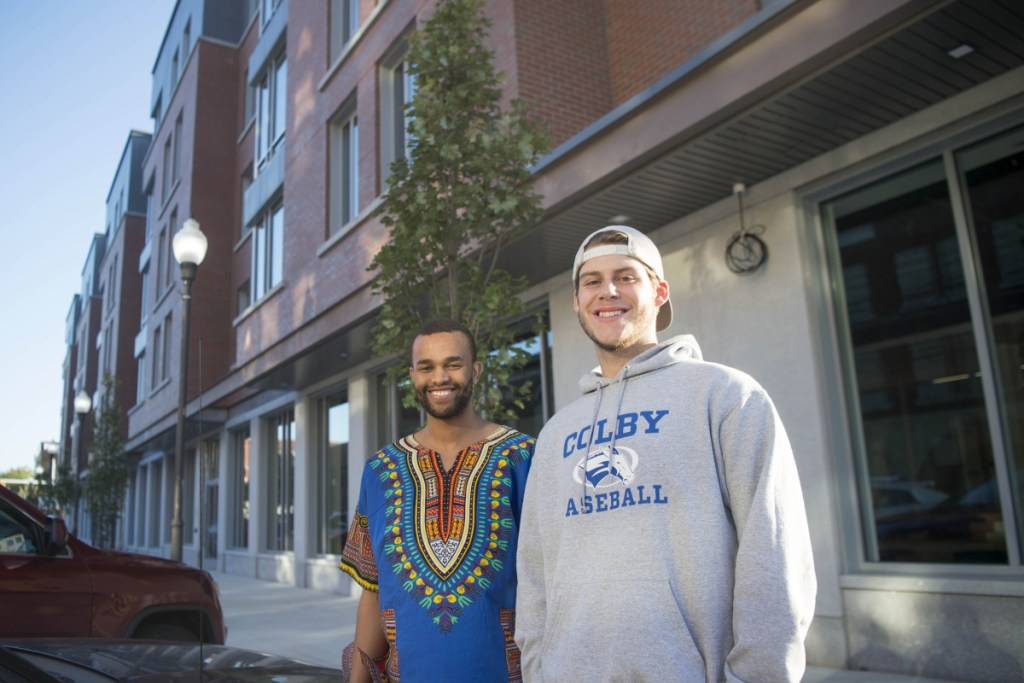 Colby students Moeketsi Justice Mokobocho, left, and Matt Reasor, right, stand for a picture in front of the new Colby College dormitory on Main Street in downtown Waterville on Friday.