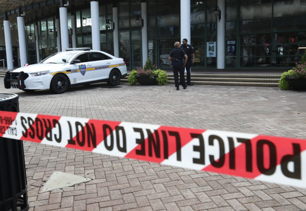Jacksonville police officers guard an area near the scene of a fatal shooting at The Jacksonville Landing in Jacksonville, Fla. A gunman opened fire at a video game tournament killing multiple people and then fatally shooting himself in a rampage that wounded several others.