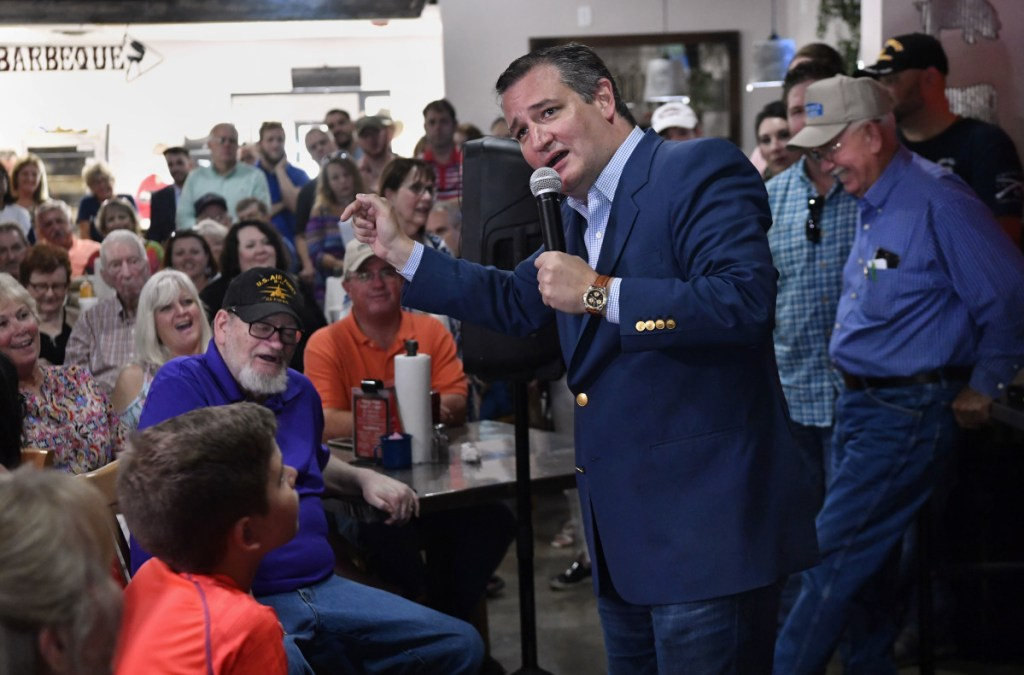 Listeners laugh as U.S. Sen. Ted Cruz jokes about the Democratic Party during a campaign stop Thursday in Abilene, Texas. President Trump will headline a rally in October for the man who has called him 'a sniveling coward.'
