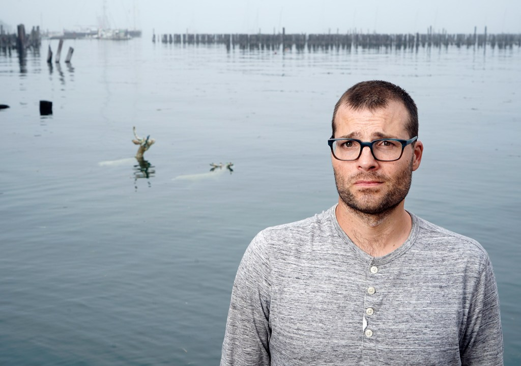 Two deer sculptures that Andy Rosen placed in Portland Harbor near the Ocean Gateway terminal in Portland are visible behind him. His project, funded with a grant from the Union of Concerned Scientists, illustrates that rising sea levels are claiming land that animals and people depend on.