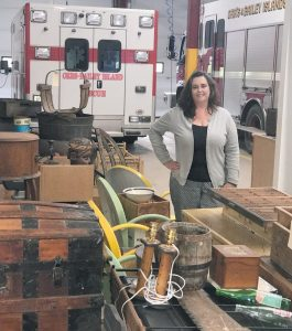 CHRISTINE DONOVAN-HALL stands by auction items at the fire station on Orr's Island. The auction is a critical piece of fundraising for the department. CONTRIBUTED PHOTO / ORR'S & BAILEY ISLANDS FIRE DEPARTMENT