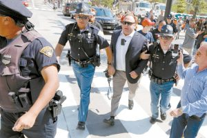 ALEX JONES, center right, is escorted by police out of a crowd of protesters outside the Republican convention in Cleveland in this July 19, 2016 file photo. AP FILE PHOTO / JOHN MINCHILLO