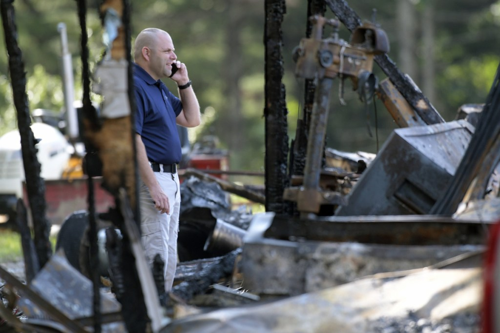 A investigator with the Office of the State Fire Marshal on Wednesday examines a residence destroyed by fire on Hunts Meadow Road in Whitefield.