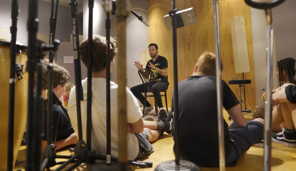 Dave Gutter, a founding member of Rustic Overtones and currently performing with the Portland band Armies,  talks with students in a songwriting camp.