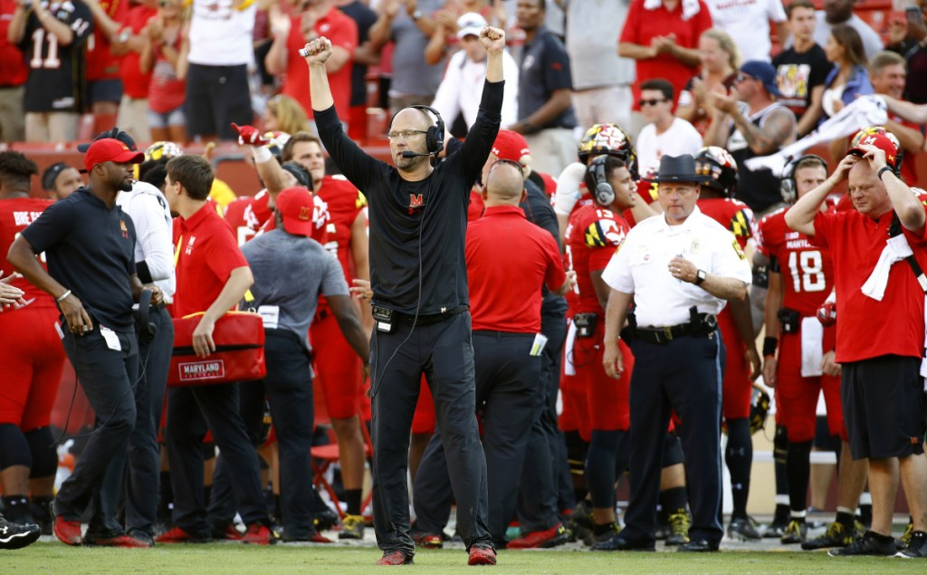 Maryland interim coach Matt Canada, center, celebrates in the final moments of the Terrapins' 34-29 upset over No. 23 Texas on Saturday in Landover, Maryland. The Terrapins had a rocky offseason, which included the death of offensive lineman Jordan McNair and charges of bullying by the coaching staff.