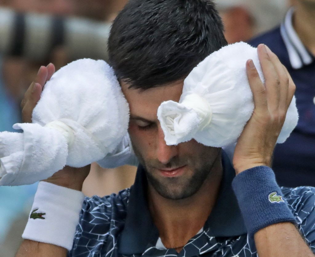 Novak Djokovic puts an ice towel around his head during a changeover against Joao Sousa during their fourth-round match on Monday. Djokovic won 6-3, 6-4, 6-3.