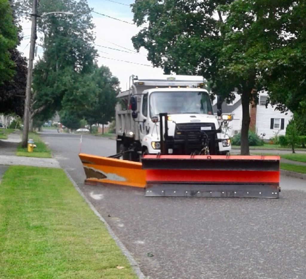 A Portland Public Works truck plows a dry, sun-warmed residential street last week, fetching puzzled looks from residents.