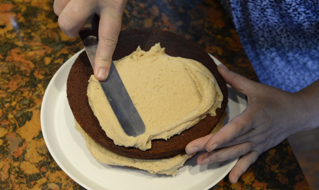 Christine Burns Rudalevige spreads peanut butter-cream cheese frosting – a family favorite – on Maine Beer Velvet Cake.