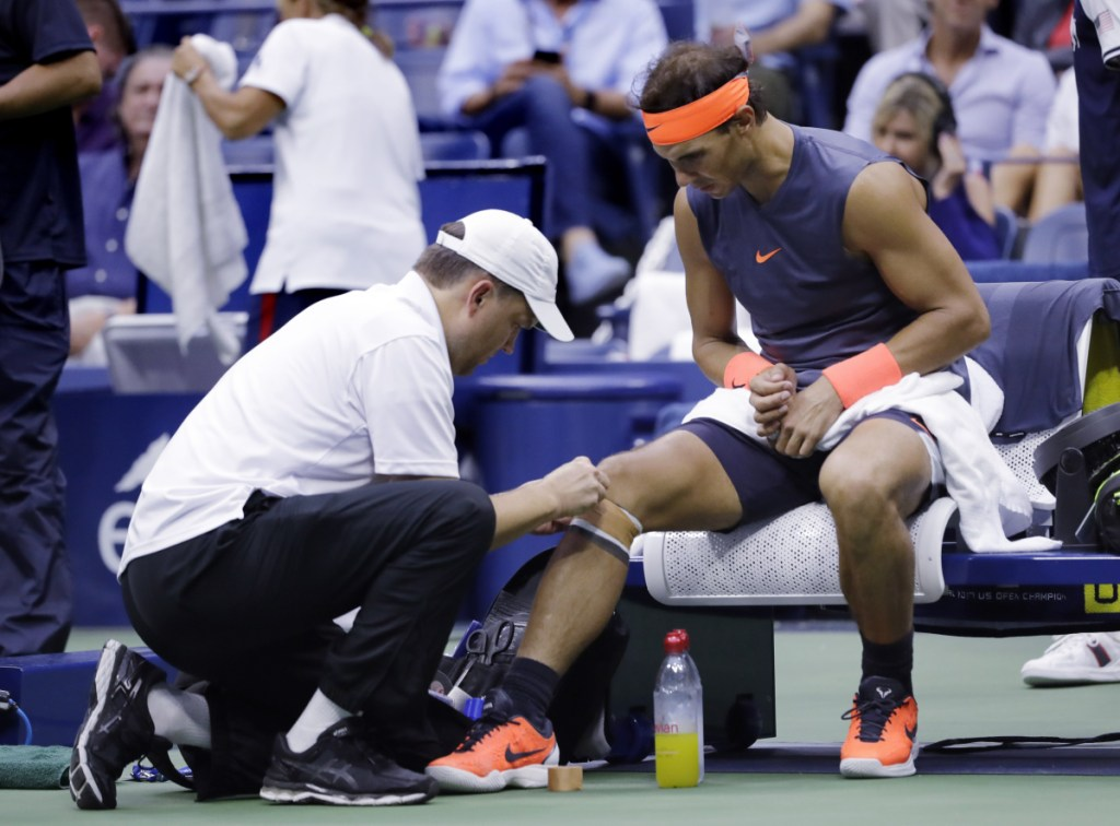 Rafael Nadal is treated by a trainer during a change over against Juan Martin del Potro during the semifinals of the U.S. Open on Friday in New York. Nadal retired after two sets because of a sore right knee.