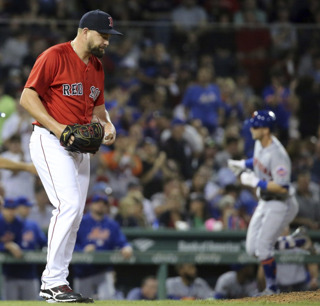 Boston reliever Brian Johnson heads back to the mound after giving up a home run to Jeff McNeil in the fourth inning. The Mets hit four homers in an 8-0 win at Fenway Park.
