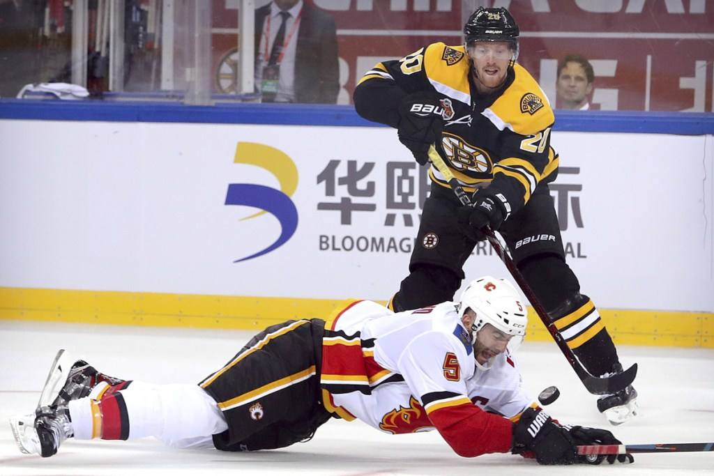 Joakim Nordstrom of the Bruins shoots on goal past Mark Giordano of the Flames during the third period Wednesday in Beijing, China. Boston beat Calgary, 3-1.