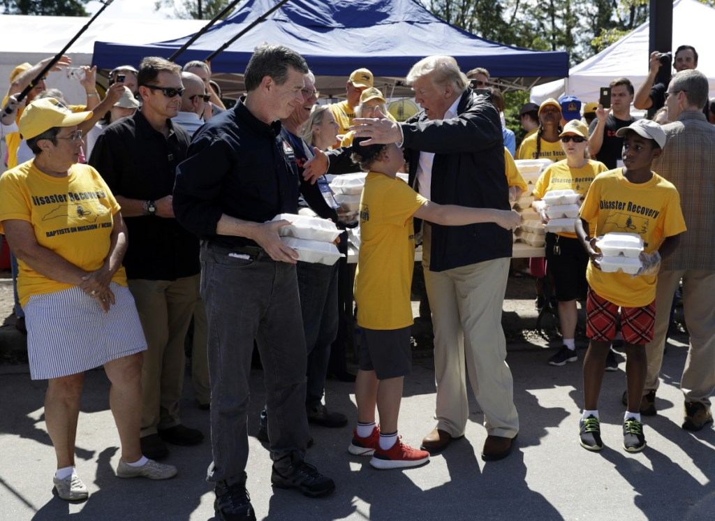 President Trump and North Carolina Gov. Roy Cooper, left, greet volunteers Wednesday as they prepare to hand out food at Temple Baptist Church in New Bern, N.C., where food and other supplies are being distributed during Hurricane Florence recovery efforts.