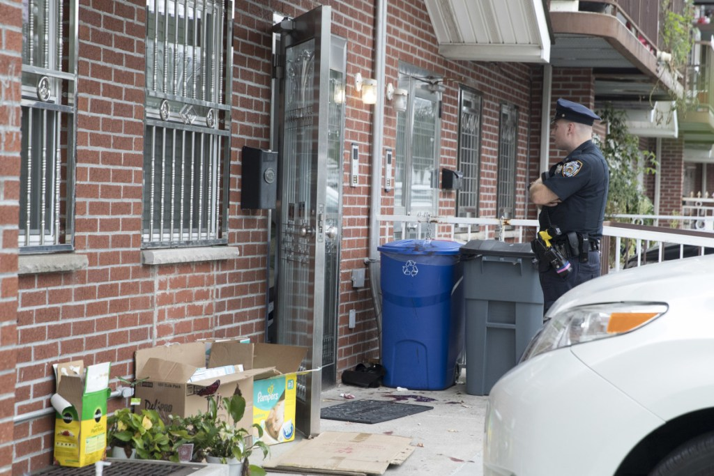A police officer stands guard at the house were five people, including three infants, were stabbed on Friday in New York.