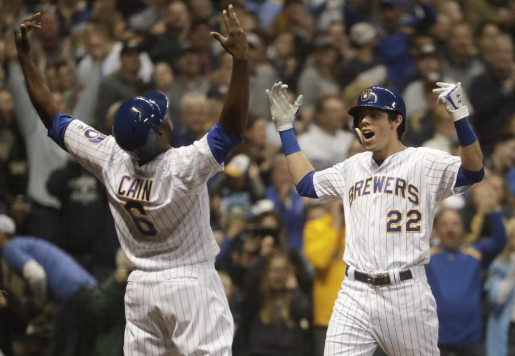 Milwaukee's Christian Yelich celebrates his two-run home run with Lorenzo Cain during the third inning against Detroit on Saturday in Milwaukee.