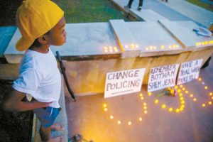 """""""YOUNG KING"""" SOLOMON GRAYSON, 6, stands on a ledge next to a memorial during a Mothers Against Police Brutality candlelight vigil for Botham Jean at the Jack Evans Police Headquarters on Friday in Dallas. Authorities are seeking a manslaughter warrant for the Dallas police officer who shot and killed Jean after she said she mistook his apartment for her own, police said Friday. SHABAN ATHUMAN / THE DALLAS MORNING NEWS VIA AP"""
