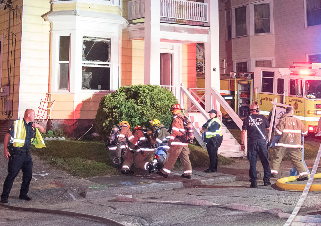Lewiston firefighters tend to the woman they pulled Thursday night from an apartment at 61 Shawmut St.