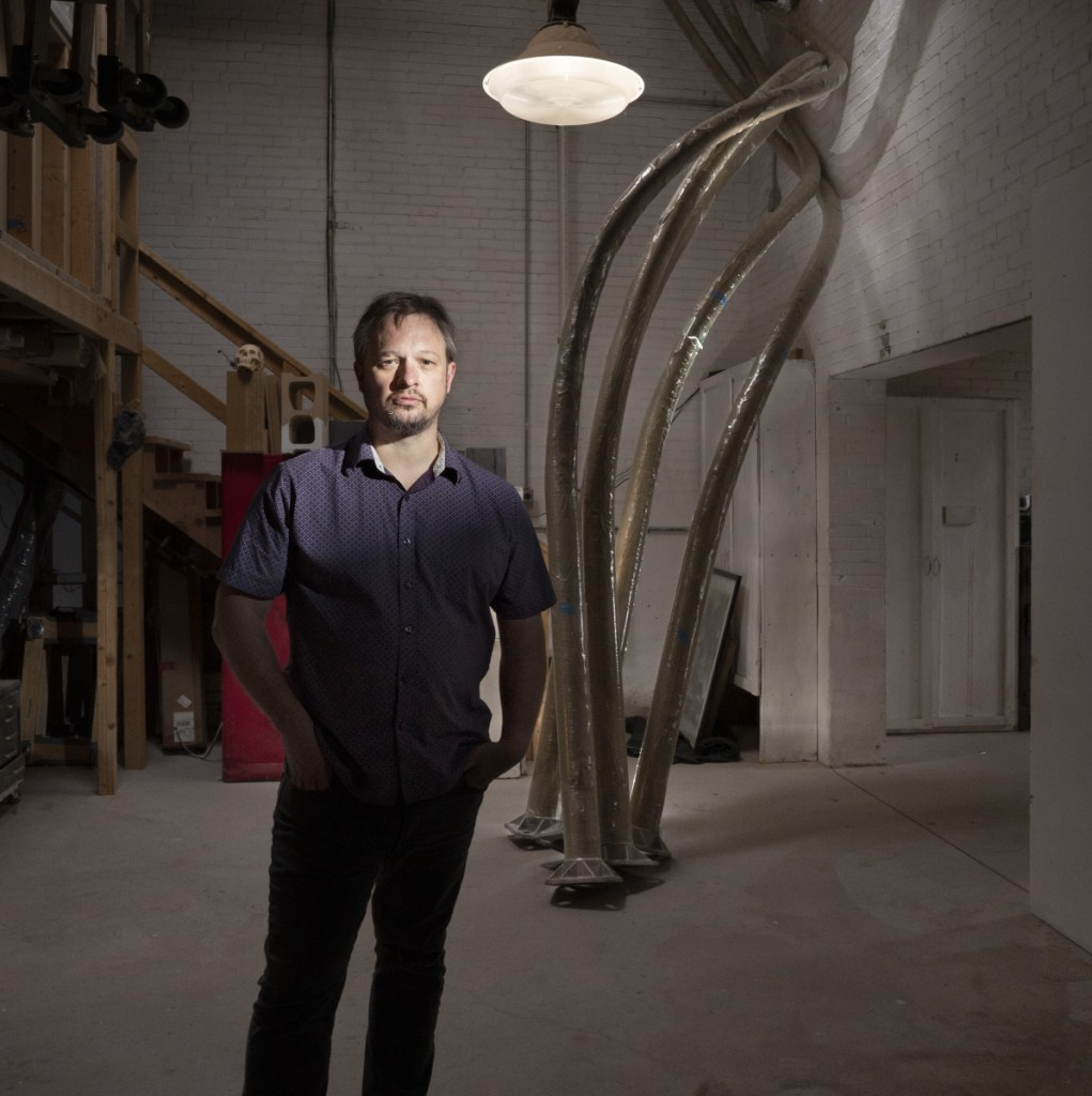 """Aaron Stephan poses with the curved poles of his sculpture  """"Luminous Arbor"""" in his Portland studio Wednesday."""