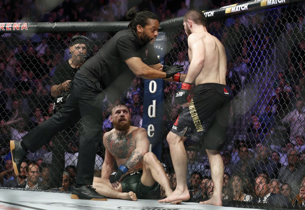 Khabib Nurmagomedov, right, is held back by referee Herb Dean after fighting Conor McGregor during a lightweight title mixed martial arts bout at UFC 229 in Las Vegas on Saturday. Nurmagomedov won the fight by submission during the fourth round to retain the title.