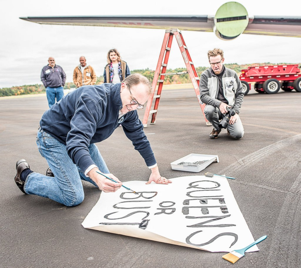 "MCR CEO Tyler Morse paints a sign, reading ""Queens or bust,"" before hanging it on the back of the 150-foot fuselage. Visitors to the plane-turned-cocktail lounge will ""feel like you walked into 1962,"" he said."