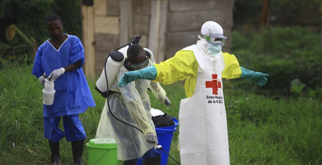 A health worker sprays disinfectant on his colleague after working at an Ebola treatment center in Beni, Congo, on Sept. 9. Nearly 100 people have died from the virus.