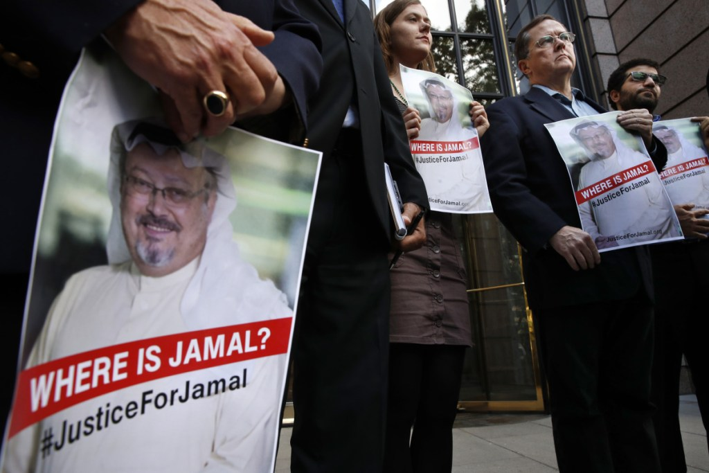 Alyssa Edling, center, and Thomas Malia, second from right, both with PEN America, join others as they hold signs of missing journalist Jamal Khashoggi, during a news conference about his disappearance in Saudi Arabia, on Oct. 10 in front of The Washington Post in Washington.