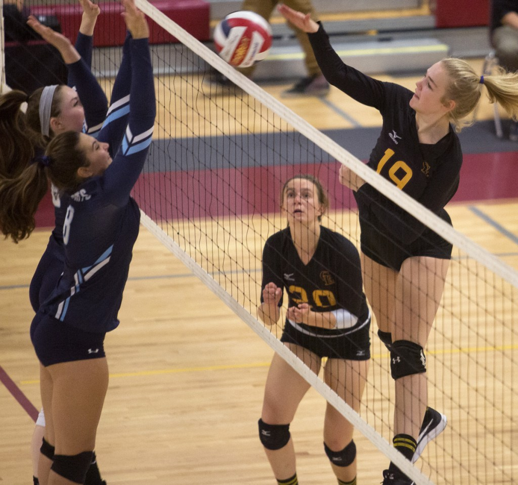 Cape Elizabeth's Bridget Heggie, right, goes up for a kill against York's Emma Parrotta, front, and Abby Orso during their Class B volleyball semifinal Wednesday night. The top-ranked Capers won 25-14, 25-16, 25-6.