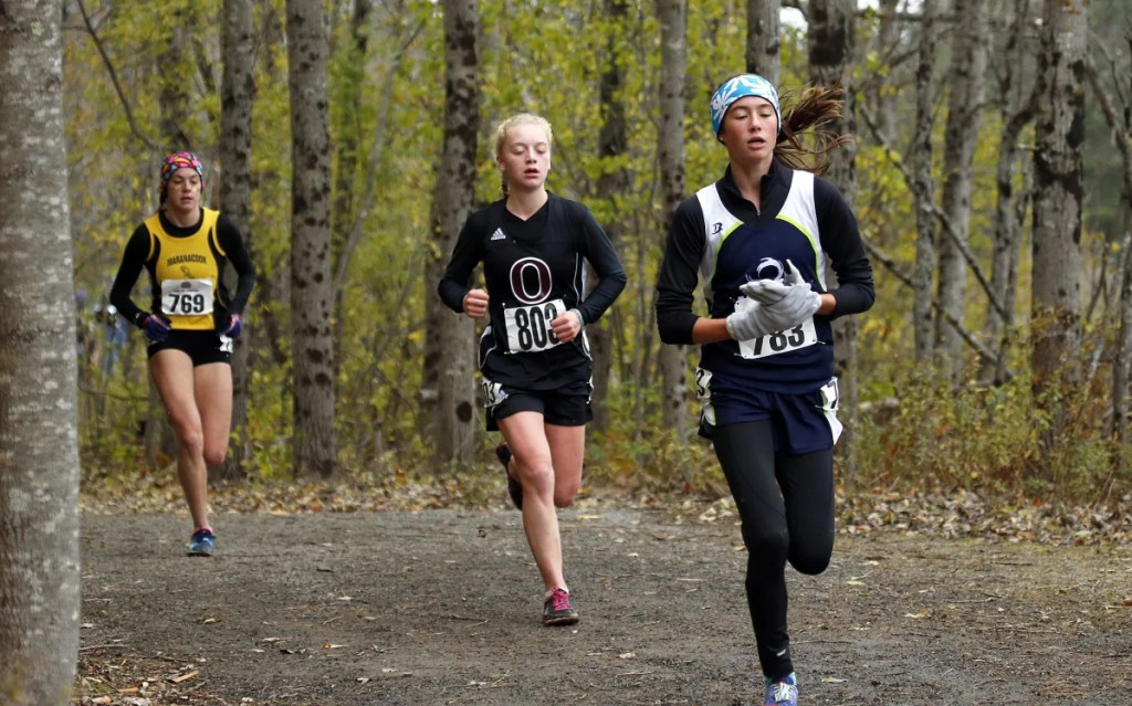 Maine Coast Waldorf's Olivia Reynolds, right, the eventual winner of the Class C cross country championships, maintains a tight lead into the backstretch at Troy A. Howard Middle School on Saturday. At her heels is Orono's Erin Gerbi, center, and Maranacook's Molly McGrail. (Staff photo by Ben McCanna/Staff Photographer)