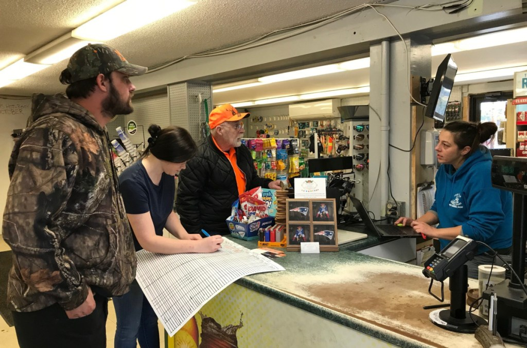 In West Gardiner, Four Corners General Store employees Dawn Hunt, right, and Jordan Shaw register Charles and Trevor Berry's deer.
