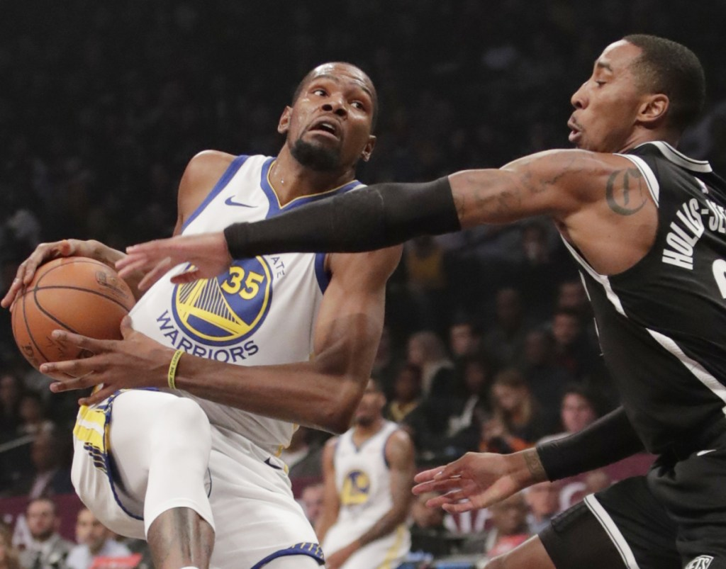 Kevin Durant of the Golden State Warriors heads to the basket Sunday against Caris LeVert of the Brooklyn Nets in the first half. Durant scored 34 in a 120-114 victory.