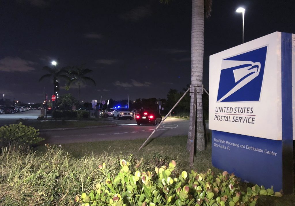 Postal service police screen employees entering the Royal Palm processing and Distribution Center on Thursday night in Opa-locka, Fla. A law enforcement source tells The Associated Press that Miami-Dade police went to the facility at the request of the FBI in connection with the mail bomb investigation.
