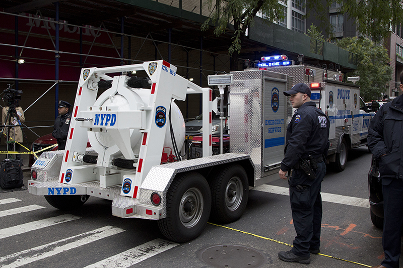 A police truck tows a total containment vessel to a post office in midtown Manhattan to dispose of a suspicious package on Friday.
